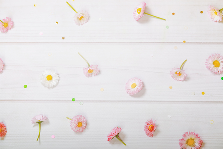Spring flowers composition for postcard. Red, yellow, white marguerite daisy and confetti in a wooden background.