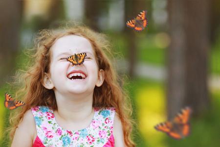 그의 코에 나비와 함께 재미있는 곱슬 소녀 웃 고. 하얀 치아와 건강 한 미소입니다. 무료 호흡 개념입니다. 스톡 콘텐츠