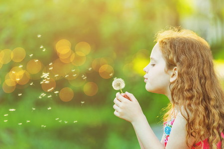 Cute child blowing dandelion in sunset light. Healthy, medical concept.