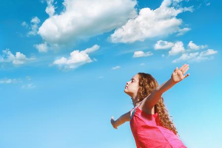 어린 소녀가 무기를 뻗어 신선한 공기를 마시고 호흡하면서 눈을 감았습니다.