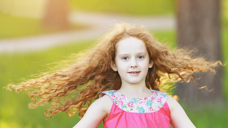 Happy little girl with a flying hairs is dancing in park.