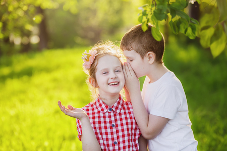 Little boy and girl whispers. Imagens