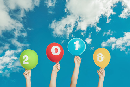 Child hand holding rainbow balloons with 2018 on blue sky and white clouds background.