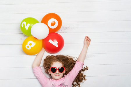 children party: Happy little girl with sunglasses, holding rainbow balloons lies on the wooden floor. New Years 2018, Christmas holiday concept. High top view.
