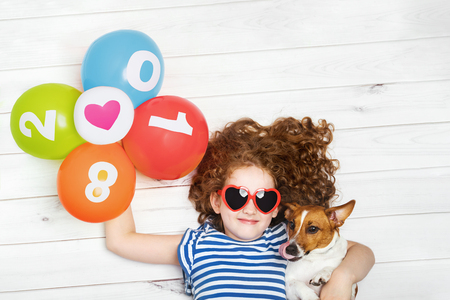 Cute girl embracing her puppy dog and holding rainbow balloons. New Years 2018, Christmas holiday concept. Lying on the wooden floor with high top view.