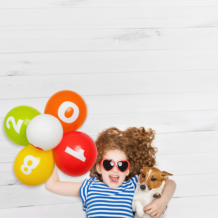 children party: Cute girl embracing her puppy dog ??and holding rainbow balloons. New Years 2018, Christmas holiday concept. Lying on the wooden floor with high top view.