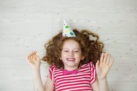 Laughing curly girl in carnival party hat, lying on a wooden floor with high top view. Happy childhood concept.