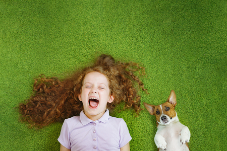 Little child and cute dog resting on green carpet. Фото со стока