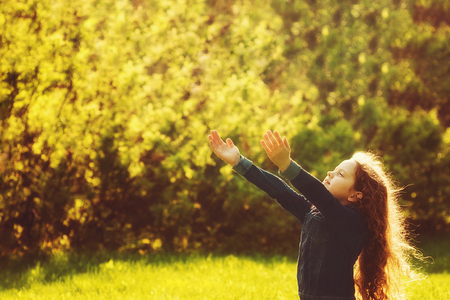 Cute little girl stretches her hand to catch sun rays. Religion, donation, people, charity, happy childhood, peace world concept. Toning instagram filter. Stock Photo
