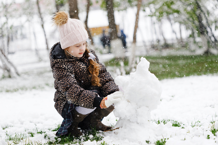 Little girl making snowman on snowy spring day.