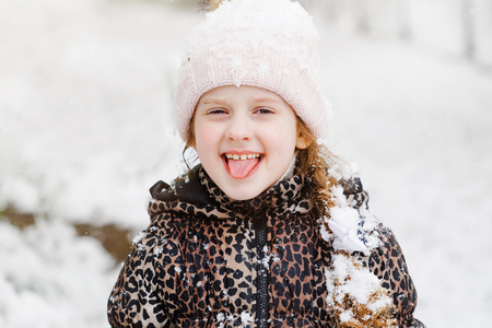 Funny girl stuck out her tongue and catches snowflakes. Happy childhood.