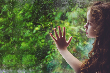 Sad child looking out the window. Toning photo. 版權商用圖片 - 82938386