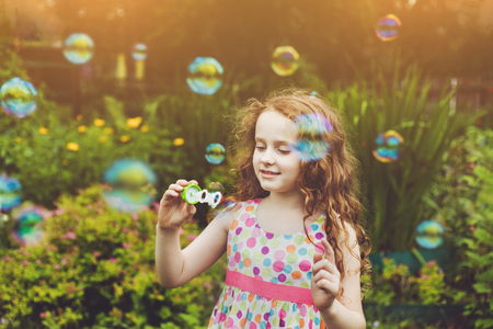 Curly little girl blowing soap bubbles in summer park.