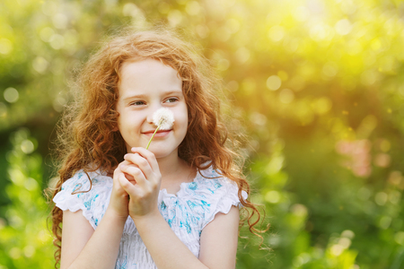 Little curly girl with white dandelion.