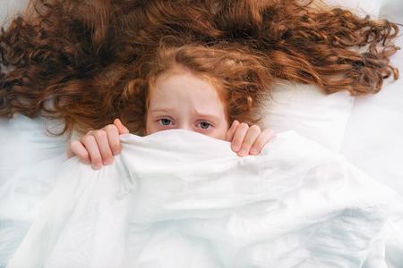 Sad little girl afraid sleeping and pulling quilt on head. Imagens
