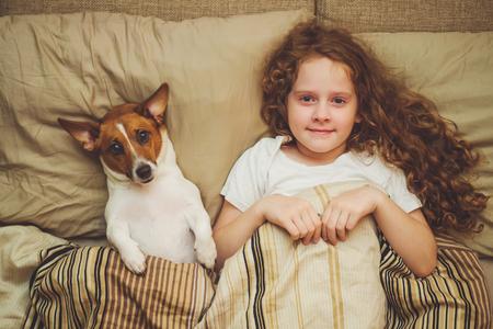 Leuk klein meisje en puppy onder dekbed. Stockfoto