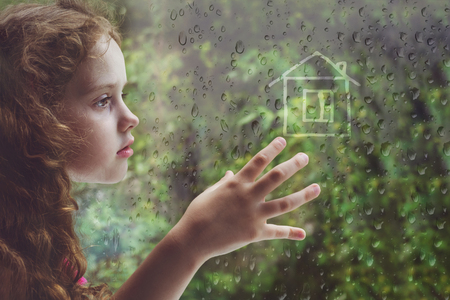 Sad curly little girl looking out the rain drop window and draw house. Toning for instagram filter.