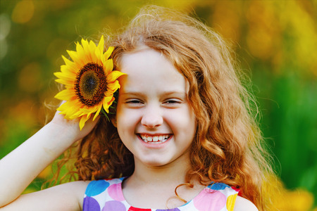 Cute little girl with sunflowers in her curly redhead hairs, enjoying nature in summer sunny day. Show white teeth. Healthcare, freedom and happy childhood concept.