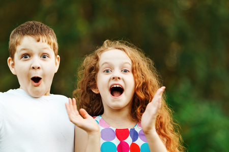 Surprised little boy and girl in summer park. Stock Photo