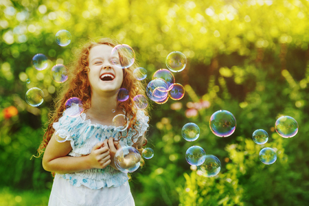 Laughing curly girl with bubbles.  Happy childhood concept. Imagens