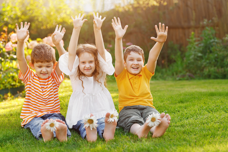 Happy friends children with daisy flowers at green grass in a summer park.  Stock Photo