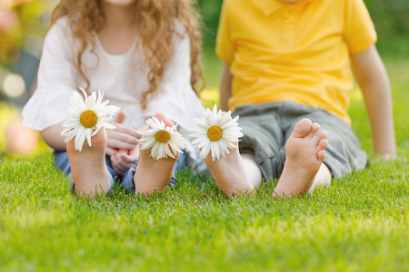 Little girl and boy with barefoot in summer park. Health, medical, happy childhood concept.