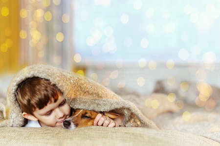 Cute baby embracing and sleeping under wool blanket in early morning christmas day. Stockfoto