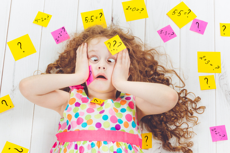 Crying child with question symbol with stickers on his head and around. Stress from learning, homework or school. Education concept.