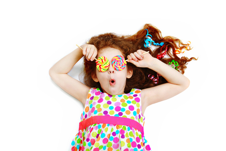 Surprised funny girl  hold candy lollipop on eyes. Stock Photo