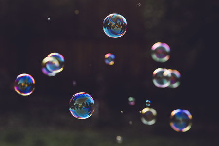 Rainbow soap bubbles on a dark background.