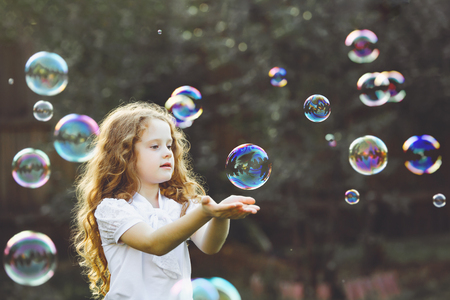Funny little girl catching soap bubbles Banco de Imagens