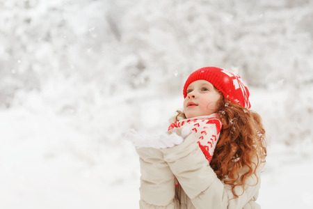 Curly hair girl catching falling snowflakes. Magic first snow. Imagens