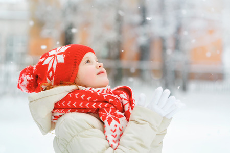Little girl in red cap catching falling snowflakes. Christmas background. Stock Photo