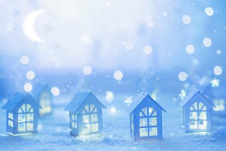 クリスマスの前の夜小さな家や星空の花輪とクリスマスの街並み。
