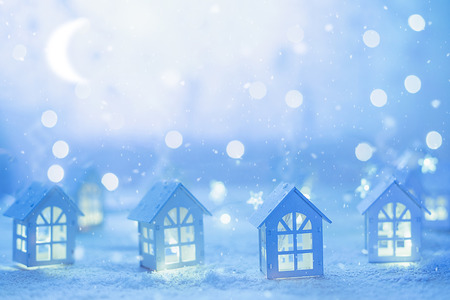 Night before Christmas. Christmas cityscape with small houses and starry garlands.