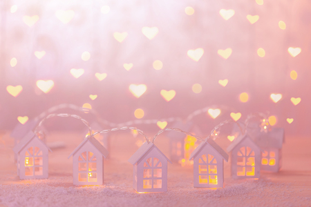 Soft focus background with small wooden houses and hearty garlands. Christmas, birthday, New Year or Valentines day holiday concept.