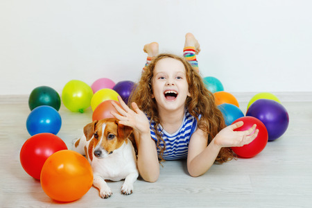 Little girl with her jack russell terrier in birthday party. Stock Photo