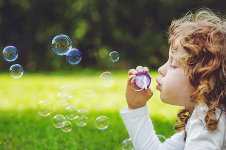 little girl blowing soap bubbles in summer park. Banco de Imagens - 91381156