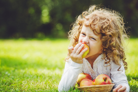 Little girl is eating apple in summer park.