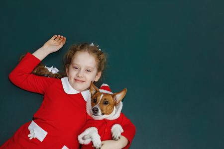 Santa girl embracing puppy dog. Christmas, New year holiday concept. Stock Photo