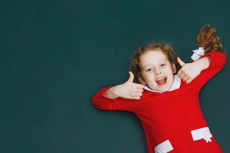 Het lachende meisje in het rode kleding tonen beduimelt omhoog. Geven zoals, vakantie, Kerstmis, Nieuwjaarconcept.