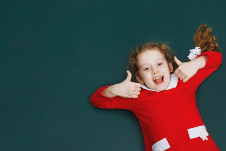 Laughing girl in red dress  showing thumbs up. Give like, holiday, Christmas, New Year concept.