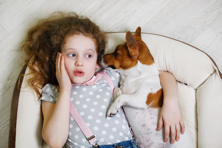 Curly girl and her puppy jack russell whispers on wood background.
