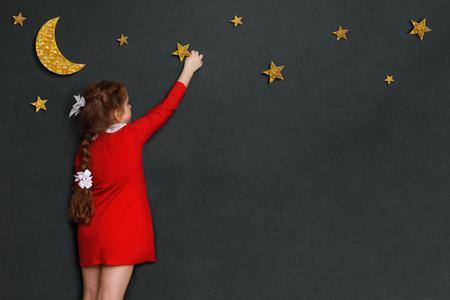 빨간 드레스에 곱슬 소녀는 별과 하늘에서 달에 밖으로 도달. 소원과 꿈꾸는 개념 좋은 밤. 스톡 콘텐츠