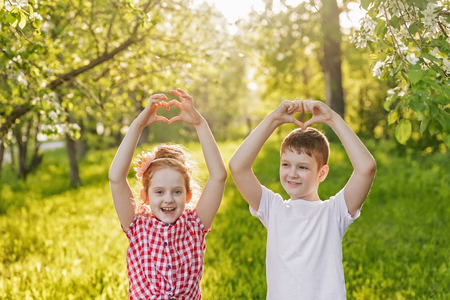 Cute little girl and boy friend folded her hands a heart shaped. Stock Photo