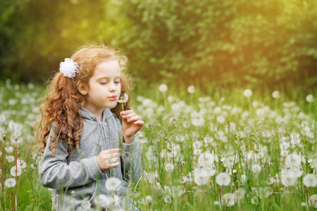 Cute curly girl blowing dandelion in spring park. Spring concept.