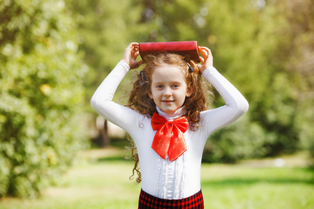 Intelligentes kleines Mädchen mit Buch in ihrem Kopf , der draußen genießt . Zurück zum Schulkonzept Standard-Bild - 92923138