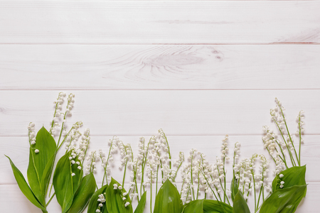 Spring flowers Lily of the valley in wooden background.