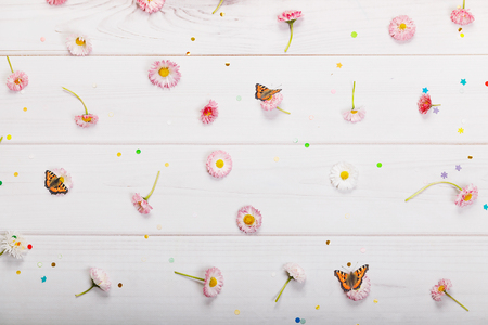 Purple, white marguerite daisy flowers and confetti in wooden background. Spring background.