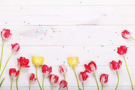Red, yellow tulips flowers, butterfly and confetti in wooden background. Hello spring concept.
